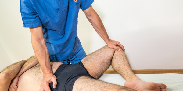 Doctor physiotherapist assisting a male patient while giving exercising treatment massaging the hip valley of patient in a physio room, rehabilitation physiotherapy concept.